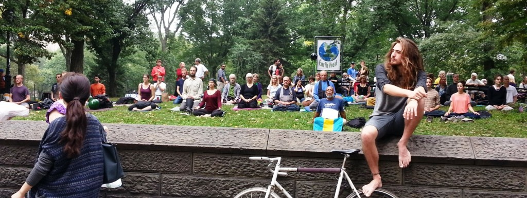 "Meditators in Central Park. Sign reads ""Earth Vigil"""